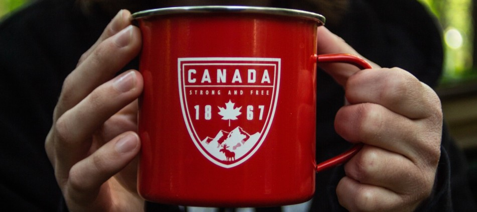 Man holding a red Canada metal cup in the forest