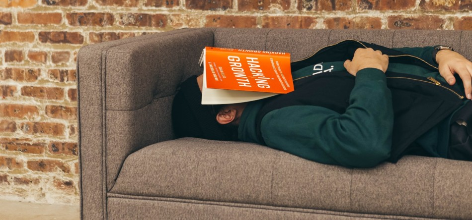 Student with book over his face sleeping on the sofa