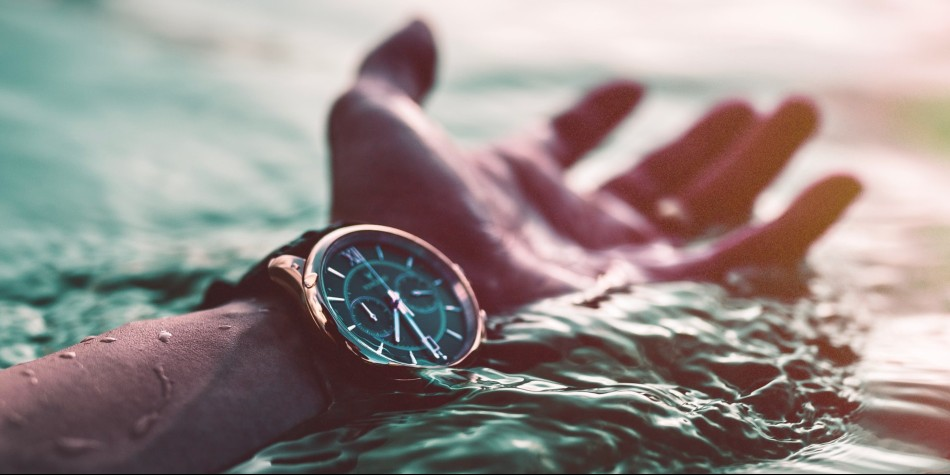 Hand and watch showing time in the water