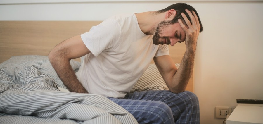 Man sitting up in bed holding head | Waklert Side Effects Explained