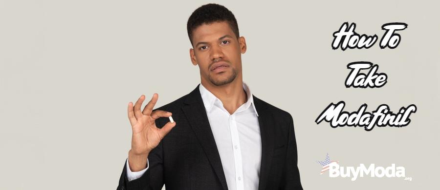 Black man holding modafinil tablet   Taking Modafinil for Narcolepsy   Buymoda