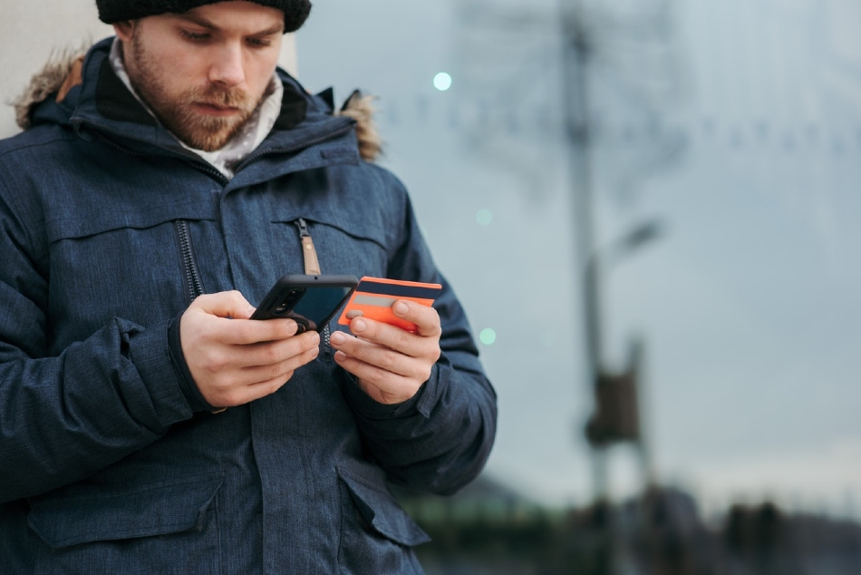 Australian man in beanie and jacket buying modafinil online using his phone