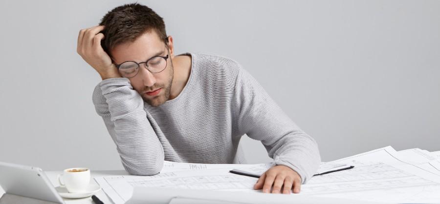 Tired man falls asleep at desk while working