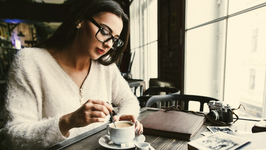 Photographer relaxing in coffee shop stirring her drink