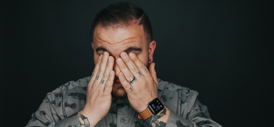 tired tattooed man in grey shirt covering face with hands