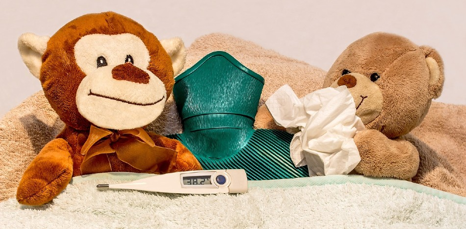 Teddy bears sick in bed with hot water bottle thermometer and tissue