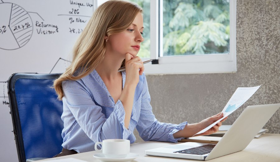 woman sitting at desk looking at data | understanding effects of modafinil and coffee