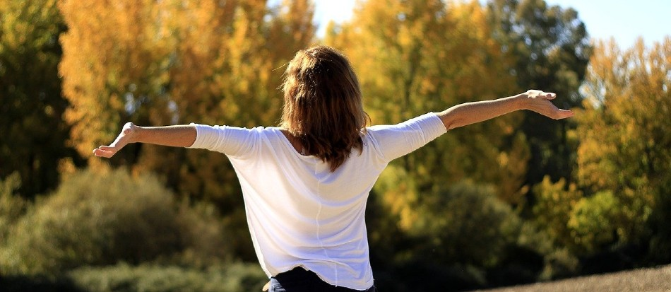 Woman with back facing camera has arms stretched out embracing the sunshine